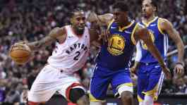 Pemain Toronto Raptors, Kawhi Leonard berusaja mempertahankan bola dari pemain Golden State Warriors, Kevin Looney dalam final pertama basket NBA di Toronto, Kamis malam 30 Juni 2019. (The Guardian/AP/Frank Gunn)